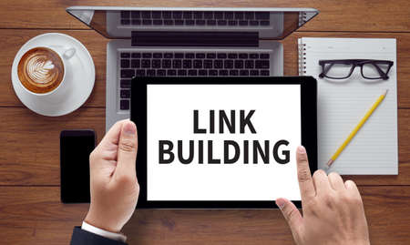 link building: LINK BUILDING, on the tablet pc screen held by businessman hands - online, top view