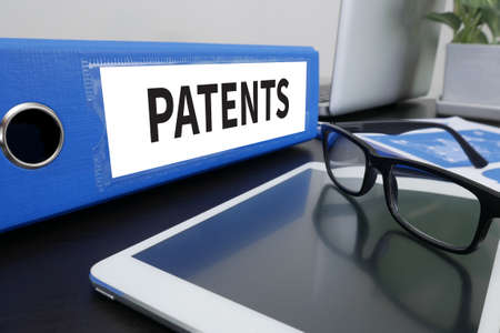 patents: PATENTS Office folder on Desktop on table with Office Supplies. ipad