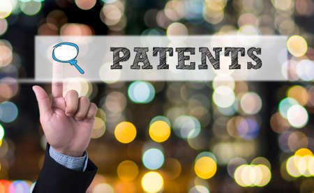 patents: PATENTS Business man with hand pressing a button on blurred abstract background