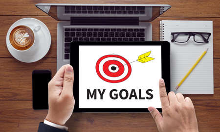 vision loss: MY GOALS, on the tablet pc screen held by businessman hands - online, top view Stock Photo