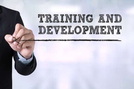 leadership development: TRAINING & DEVELOPMENT CONCEPT Businessman drawing Landing Page on blurred abstract background