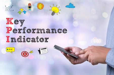 kpi: KPI acronym (Key Performance Indicator) person holding a smartphone on blurred cityscape background
