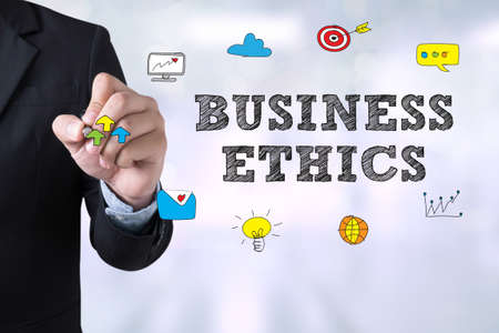 business ethics: BUSINESS ETHICS Businessman drawing Landing Page on blurred abstract background Stock Photo