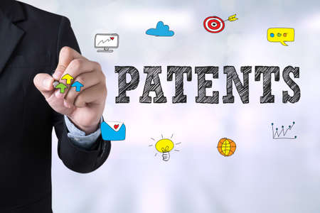 patents: PATENTS Businessman drawing Landing Page on blurred abstract background Stock Photo