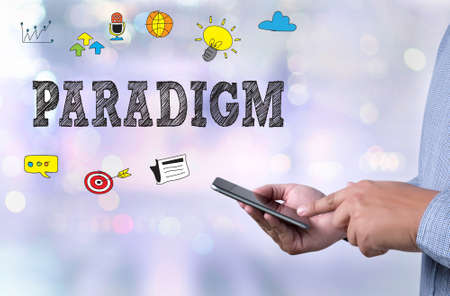 paradigm: PARADIGM person holding a smartphone on blurred cityscape background