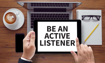 interpersonal: BE AN ACTIVE LISTENER, on the tablet pc screen held by businessman hands - online, top view Stock Photo