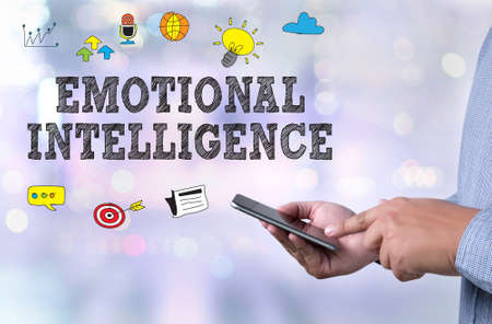 EMOTIONAL INTELLIGENCE person holding a smartphone on blurred cityscape background Stock Photo