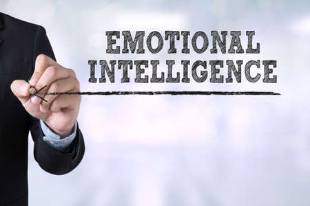 emotional intelligence: EMOTIONAL INTELLIGENCE Businessman drawing Landing Page on blurred abstract background Stock Photo