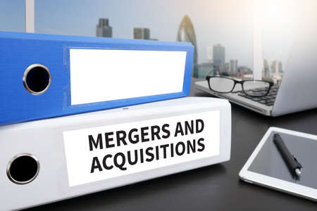 acquisitions: M&A (MERGERS AND ACQUISITIONS) Office folder on Desktop on table with Office Supplies.