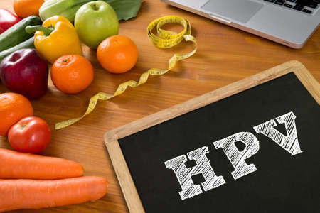 harmless: HPV CONCEPT Fitness and weight loss concept, fruit and tape measure on a wooden table, top view,