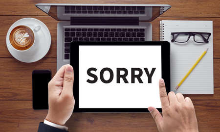 regretful: SORRY, on the tablet pc screen held by businessman hands - online, top view