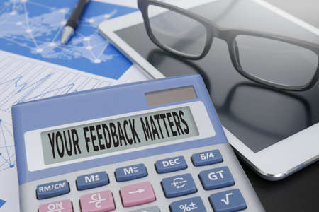 solicit: YOUR FEEDBACK MATTERS Calculator  on table with Office Supplies.