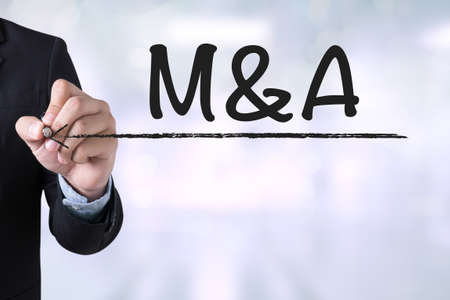 acquisitions: M&A (MERGERS AND ACQUISITIONS) Businessman drawing Landing Page on blurred abstract background