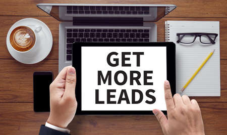 converting: GET MORE LEADS, on the tablet pc screen held by businessman hands - online, top view