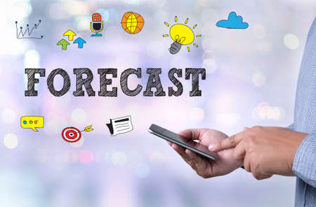 predictable: FORECAST person holding a smartphone on blurred cityscape background Stock Photo
