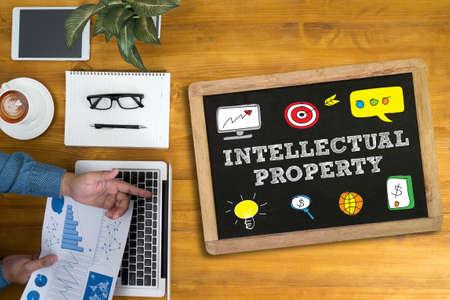 El hombre de negocios INTELECTUAL PROPIEDAD trabaja en el escritorio de oficina y usando la computadora y objetos, café, vista desde arriba,