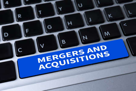 company ownership: M&A (MERGERS AND ACQUISITIONS) a message on keyboard Stock Photo