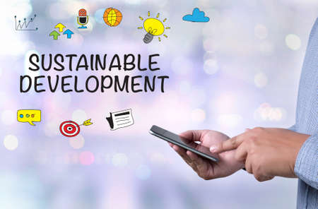 sustainable development: SUSTAINABLE DEVELOPMENT person holding a smartphone on blurred cityscape background Stock Photo
