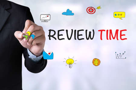reassessment: REVIEW TIME and Businessman drawing Landing Page on blackboard Stock Photo