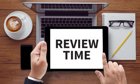 reassessment: REVIEW TIME, on the tablet pc screen held by businessman hands - online, top view