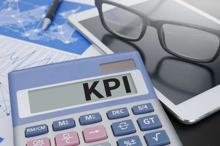 kpi: KPI CONCEPT Calculator on table with Office Supplies.