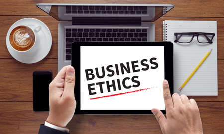 work ethic responsibilities: BUSINESS ETHICS, on the tablet pc screen held by businessman hands - online, top view Stock Photo