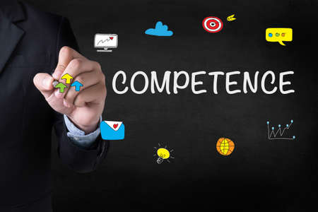 competence: COMPETENCE Businessman drawing Landing Page on blurred abstract background Stock Photo