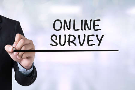 electronic survey: ONLINE SURVEY Businessman drawing Landing Page on blurred abstract background