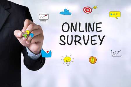 appraise: ONLINE SURVEY and Businessman drawing Landing Page on blackboard Stock Photo