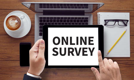 appraise: ONLINE SURVEY, on the tablet pc screen held by businessman hands - online, top view Stock Photo