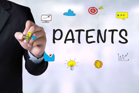patents: PATENTS and Businessman drawing Landing Page on blackboard