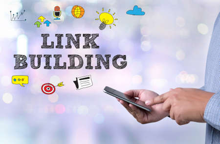 LINK BUILDING person holding a smartphone on blurred cityscape background