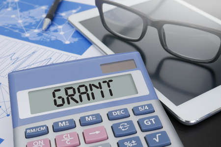 GRANT Calculator on table with Office Supplies.