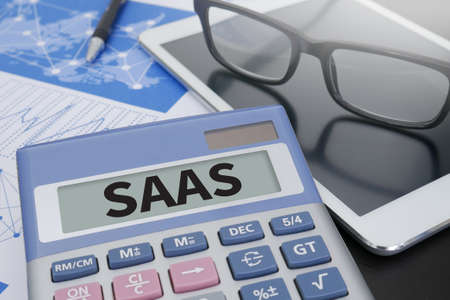 saas fee: SAAS Calculator on table with Office Supplies. Stock Photo