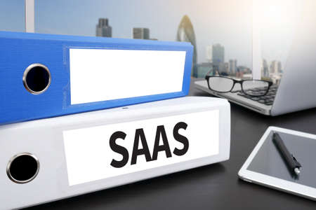saas fee: SAAS Office folder on Desktop on table with Office Supplies. Stock Photo