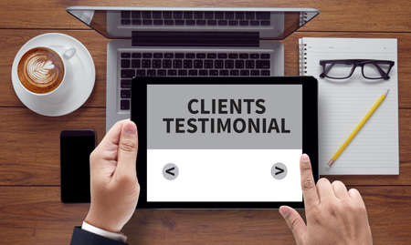 affirmations: CLIENTS TESTIMONIAL, on the tablet pc screen held by businessman hands - online, top view Stock Photo