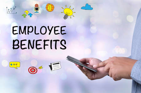 additional compensation: EMPLOYEE BENEFITS person holding a smartphone on blurred cityscape background