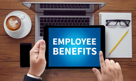 additional compensation: EMPLOYEE BENEFITS, on the tablet pc screen held by businessman hands - online, top view
