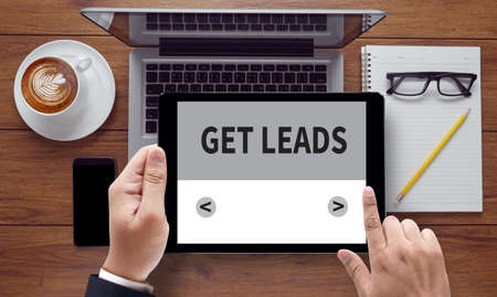 leadership key: GET LEADS, on the tablet pc screen held by businessman hands - online, top view