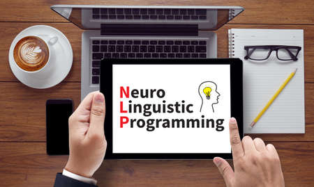 linguistic: NLP Neuro Linguistic Programming, on the tablet pc screen held by businessman hands - online, top view Stock Photo