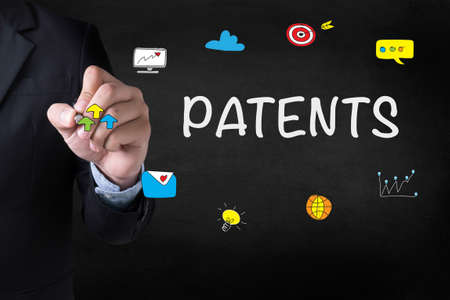 patents: PATENTS Businessman drawing on blurred abstract background Stock Photo