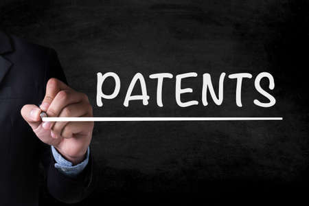 patents: PATENTS and Businessman drawing on blackboard