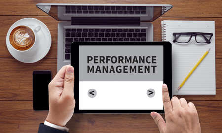 intervenes: PERFORMANCE MANAGEMENT, on the tablet pc screen held by businessman hands, top view