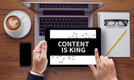 CONTENT IS KING concept on the tablet pc screen held by businessman hands, top view