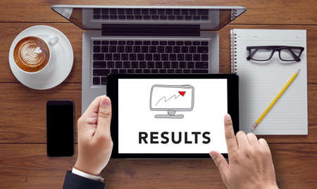 consequence: RESULTS Concept on the tablet pc screen held by businessman hands, top view Stock Photo