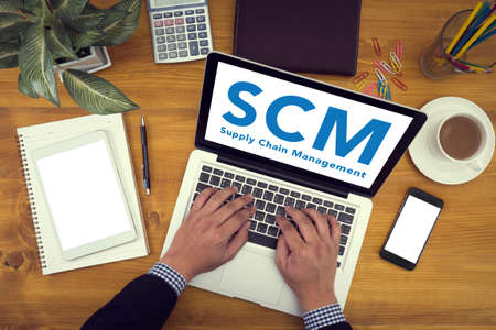 scm: SCM Supply Chain Management concept Corporate identity mock up on an hardwood desk with laptop, tablet, smartphone and a cup of coffee Stock Photo