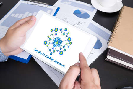 scm: SCM Supply Chain Management concept Modern people doing business, graphs and charts and touch-pad Stock Photo