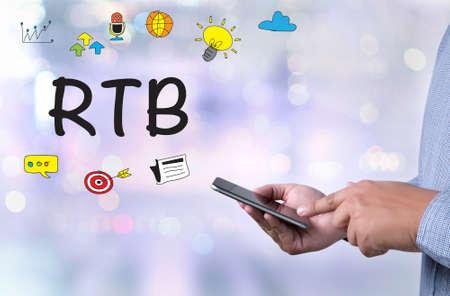 stock ticker board: RTB concept, person holding a smartphone on blurred cityscape background