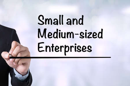 enterprises: SME or Small and medium-sized enterprises Businessman drawing Landing Page on blurred abstract background