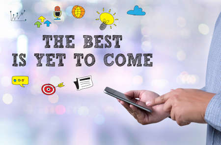 the next life: THE BEST IS YET TO COME person holding a smartphone on blurred cityscape background Stock Photo